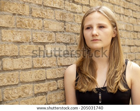 Young teenage girl looking sad or depressed in front of a brick wall background - stock photo
