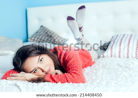 Young teenage girl lying in bed, relaxing, looking at camera - stock photo