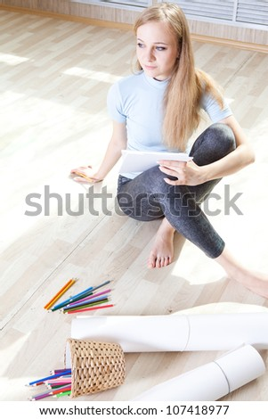 young teenage girl on the floor thinking and drawing