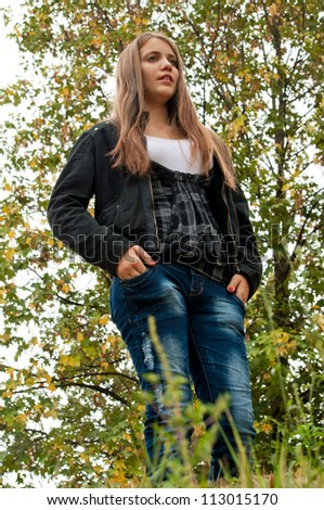 Young teenage girl posing in the park at autumn - shot from the ground - stock photo