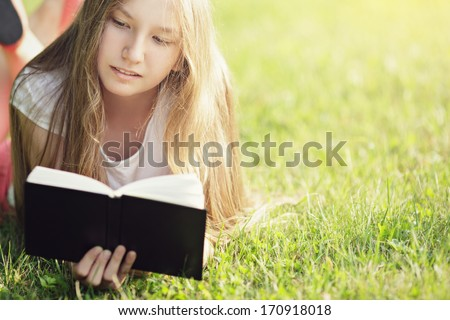 young teenage girl reading book on grass, summertime lifestile - stock photo