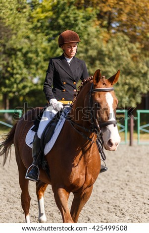 Young teenage girl riding a horse. Equestrian sportswoman jockey - stock photo