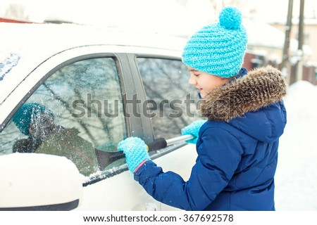 Young teenage girl scraping ice on car window from winter snow in january. Bright outdoors horizontal image - stock photo