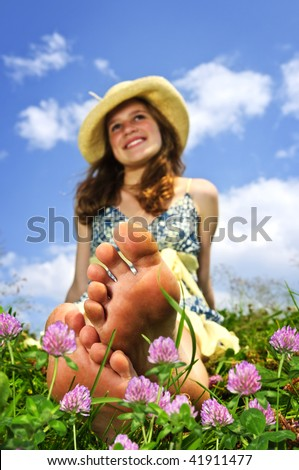 Young teenage girl sitting on summer meadow amid wildflowers in straw hat