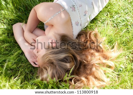 Young teenage girl sleeping while laying down on long green grass in a garden during the summer. - stock photo