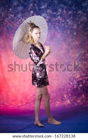 young teenage girl standing in floral kimono in studio