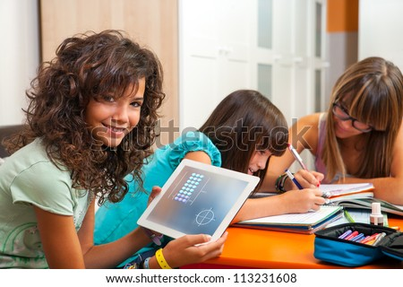 Young teenage girl with classmates showing homework on digital tablet. - stock photo