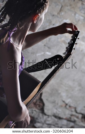 Young teenage girl with musical instrument guitar, tuning it against old brick wall.  - stock photo