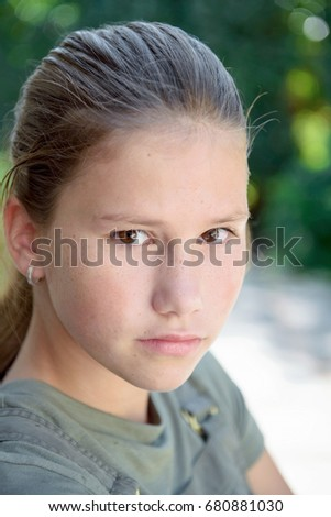 young teenage girl with ponytail outside in garden.