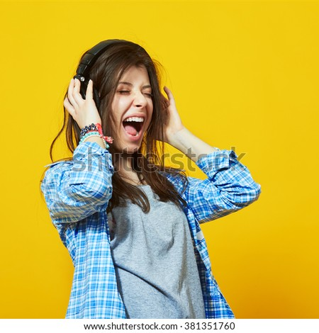 young teenage woman wearing headphones listen to music and sing with open mouth over colorful yellow background - stock photo