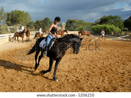 young teenager and her black horse in a training of jumping competition - stock photo