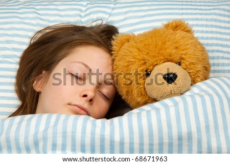 Young Teenager Asleep in Bed with Teddy Bear - stock photo