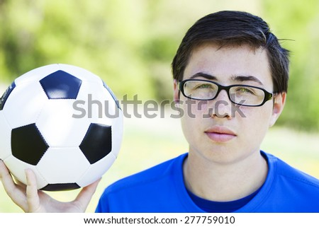 Young teenager boy with soccer ball in natural environment  - stock photo