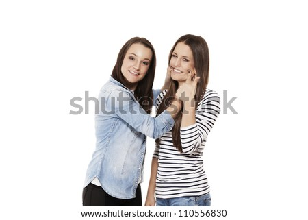 young teenager forcing her friend to laugh on white background - stock photo