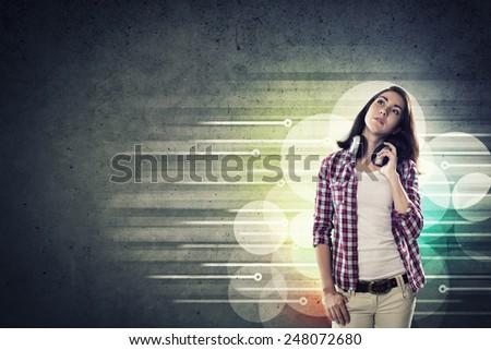 Young teenager girl in shirt wearing headphones - stock photo