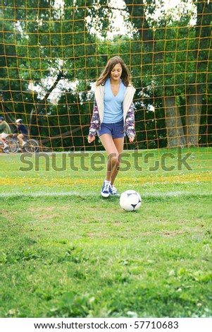 Young teenager girl playing with a soccer ball