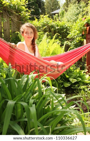 Young teenager girl sit in a red hammock into a garden