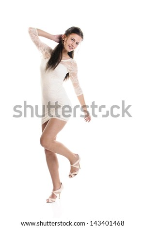 Young teenager girl wearing a short white dress and white high heels and dancing isolated against white background.
