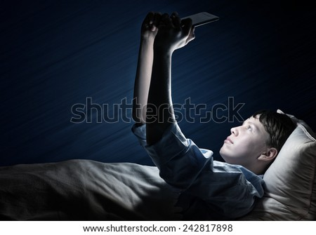Young teenager guy in bed using tablet pc - stock photo