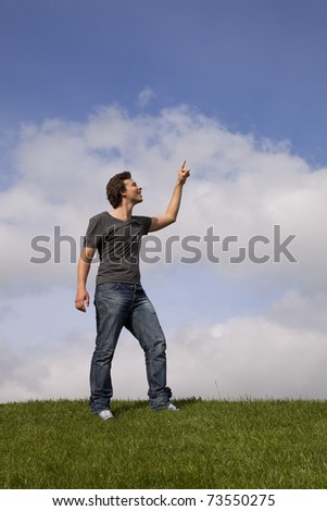 young teenager pointing to the copy space - stock photo