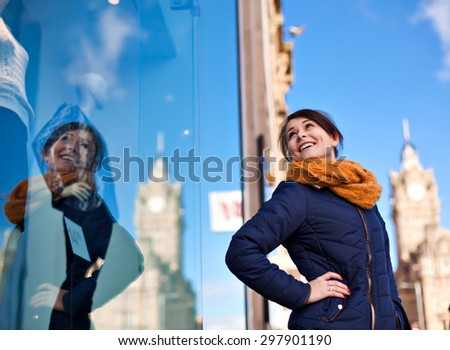 Young teenager pretty girl looking at the clothes in a fashion store shop window in the city, thinking about buying new garments.  - stock photo