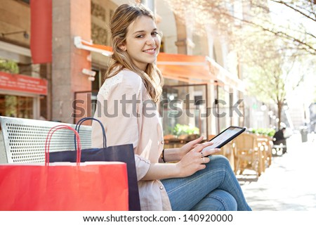 Young teenager student girl sitting on a bench in the city center using a digital tablet technology device with her shopping paper bags, smiling. - stock photo