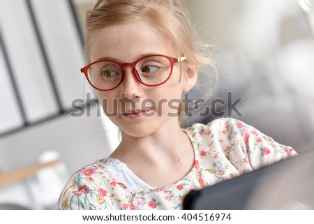 Young teenager with eyeglasses using tablet