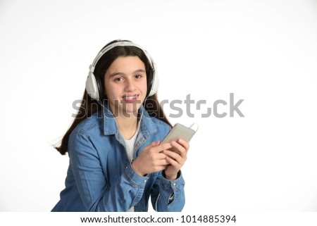 Young teenager with his headphones, listening to music through the mobile.
