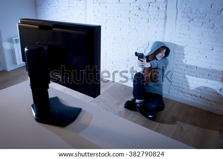 young teenager woman abused suffering internet cyberbullying scared and desperate defending herself pointing gun to computer monitor in cyber bullying concept - stock photo