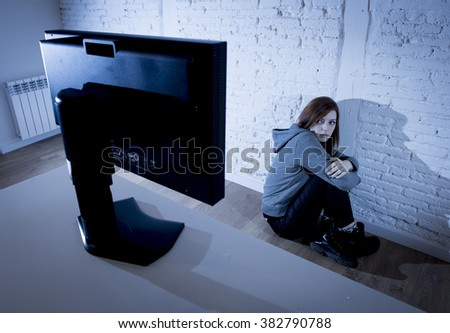 young teenager woman abused suffering internet cyberbullying scared sad and depressed in fear face expression sitting on the floor in front of computer monitor in cyber bullying social problem concept - stock photo
