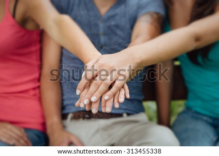 Young teenagers sitting on a wooden bench and stacking hands, friendship and cooperation concept