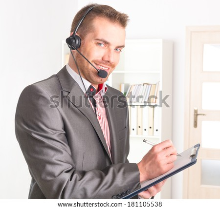 young Telephone Operator with a headset and notepad in call center - stock photo