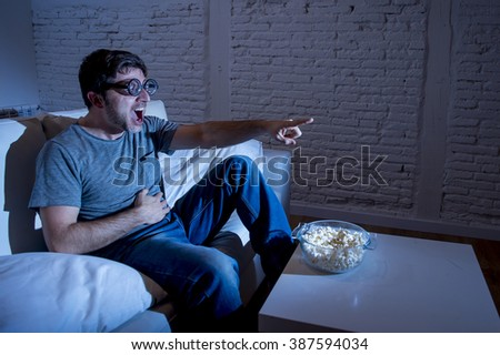 young television addict man sitting on home sofa watching TV and eating popcorn wearing funny nerd and geek glasses laughing crazy enjoying comedy movie or sitcom at night - stock photo
