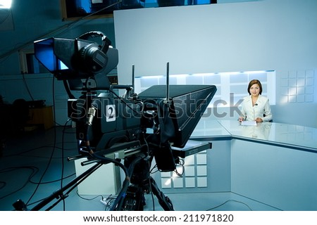 young television announcer at studio during live broadcasting - stock photo