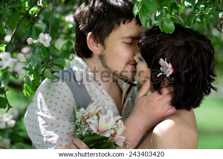 Young tenderness couple relax in blossom garden - stock photo