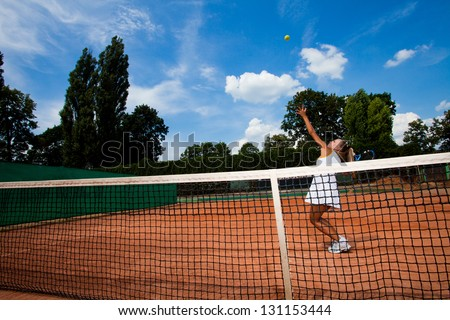 Young tennis player hitting a ball over the net on the court - stock photo