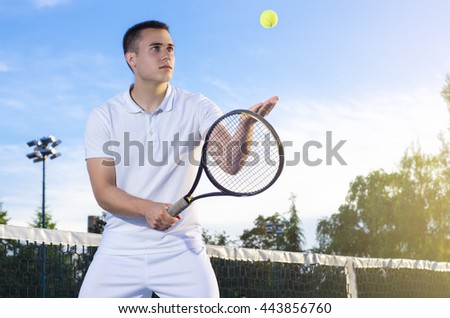 Young tennis player throwing ball in the air, serving, selective focus on eyes