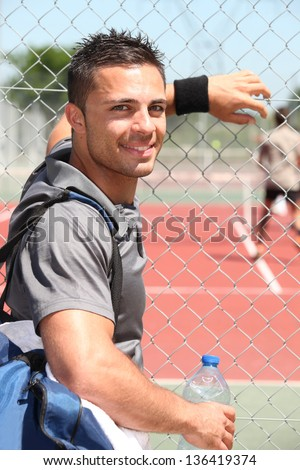 Young tennis player watching a game - stock photo
