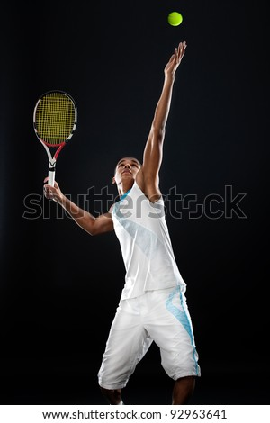 Young tennis player with racket ready to serve a tennis ball - stock photo