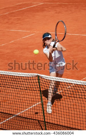 Young tennis talent hitting a volley on clay court - stock photo