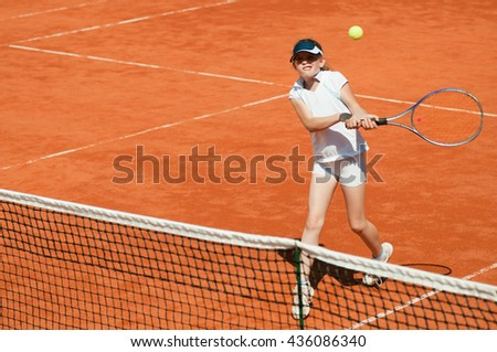 Young tennis talent hitting two-handed backend volley on the net - stock photo