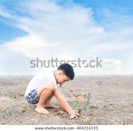 Young Thai boy planting little seedling on dry and crack empty land. Earth day concept.