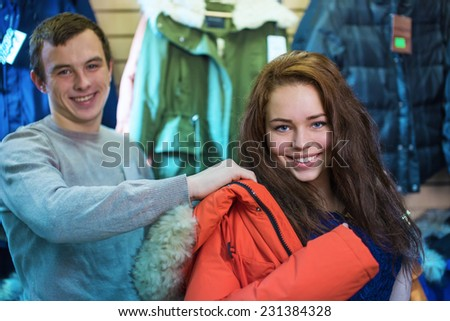 Young the man helps to put on to the girl a jacket in shop - stock photo
