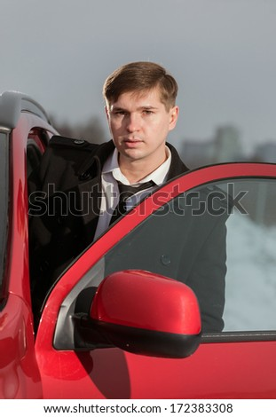 Young the man leaves the car - stock photo
