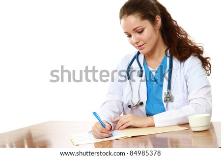 Young therapeutis writing prescription at desk isolated on white - stock photo