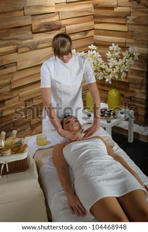 Young therapist massaging cleavage to attractive  woman at spa - stock photo
