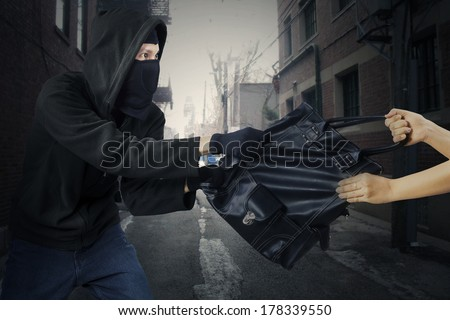 Young thief stealing woman's bag on the street - stock photo