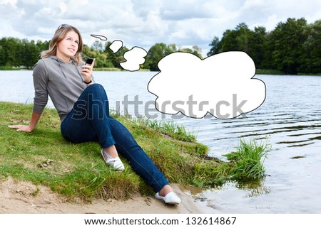 Young thinking woman with mobile phone and blank thought cloud