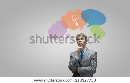 Young thoughtful businessman and colorful speech bubbles above