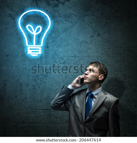 Young thoughtful businessman looking a bulb above head
